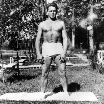 Joseph Pilates outside in nature with exercise mat