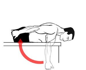Image of male laying prone on bench extending arm