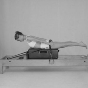 Lady doing, Pulling straps on Pilates reformer