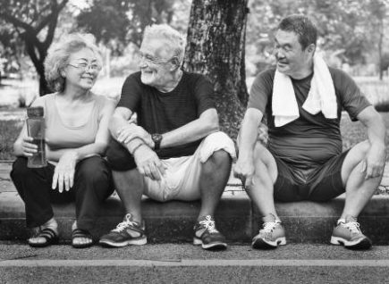 after exercising two men and a woman sit on the kerb recovering and socialising a good display of whole body health