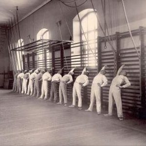 A group of men stretching on the Swedish bars at the Royal Central Institute of Gymnastics