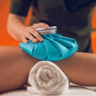 Therapist putting an ice pack on an injured patients knee