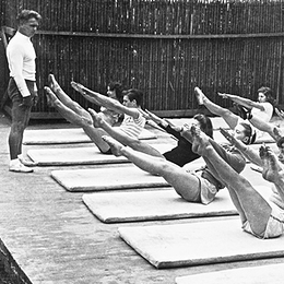 Joseph Pilates teaching the teaser exercise to a group of dancers outdoors